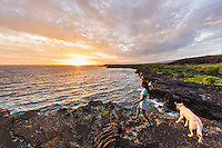 At sunset, a woman and her dog hike the historic 1871 Trail in Honanau, Big Island. The ancient trail was the main artery for coastal travel between several villages in the area.