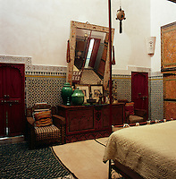 The bedroom walls are lined with decorative tiles and the floor with rustic rugs. An ornate mirror hangs above a carved wooden sideboard, which faces the four-poster bed