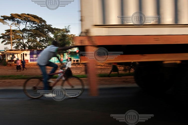 A man holds onto a truck while riding a bicycle in Nairobi.