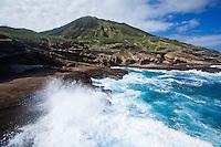 Waves crash against lava rocks near Lanai Island Lookout, with Koko Crater in the background, Hawai'i Kai, O'ahu.
