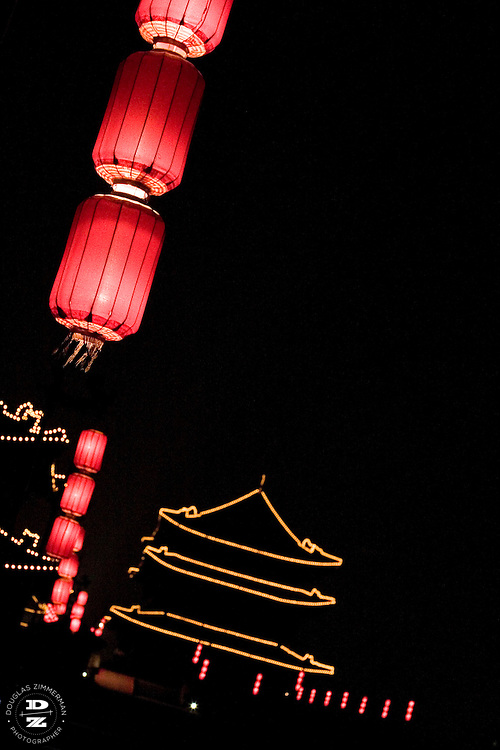 Lanterns and lights enluminate the old city wall in Xian, China. . Photograph by Douglas ZImmerman