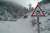 Road warning sign in the snow covered landscape in Chabanon, French Alps, France.
