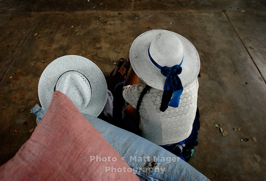 Two cocaleras sit and rest after packing coca leaves into bags in the coca market in Eterezama, Bolivia.