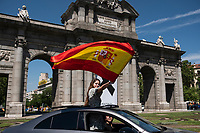MADRID, SPAIN - MAY 23: A woman waves a Spanish flag from a car in front of Puerta de Alcalá during the demonstration organized by VOX, Spanish far-right party and third biggest party in the Parliament, to demand the resign of the national Government on 23 May 2020, in Madrid, Spain. This protest, which should be participated from the car, occurs in the middle of deescalation plans of covid 19 and the state of emergency remains active due to the coronavirus. (Photo by Sergio Belena / VIEWpress).