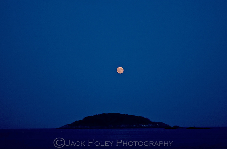 The moon rising over House Island in Manchester Bay, Massachusetts.