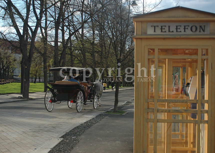 Old style telephone kiosk and a horse cart in Karlovy Vary, Czech Republic, Europe