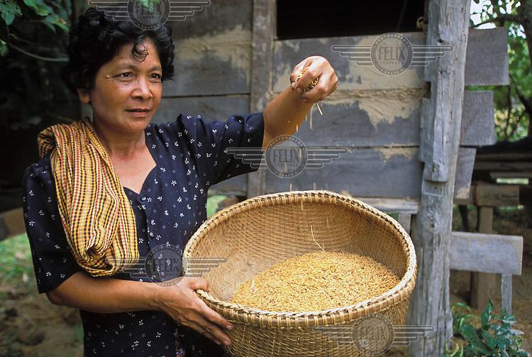 A farmer winnows her grain.