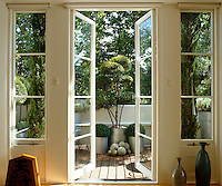 French windows open on to a small roof terrace with teak decking and plants in aluminium pots