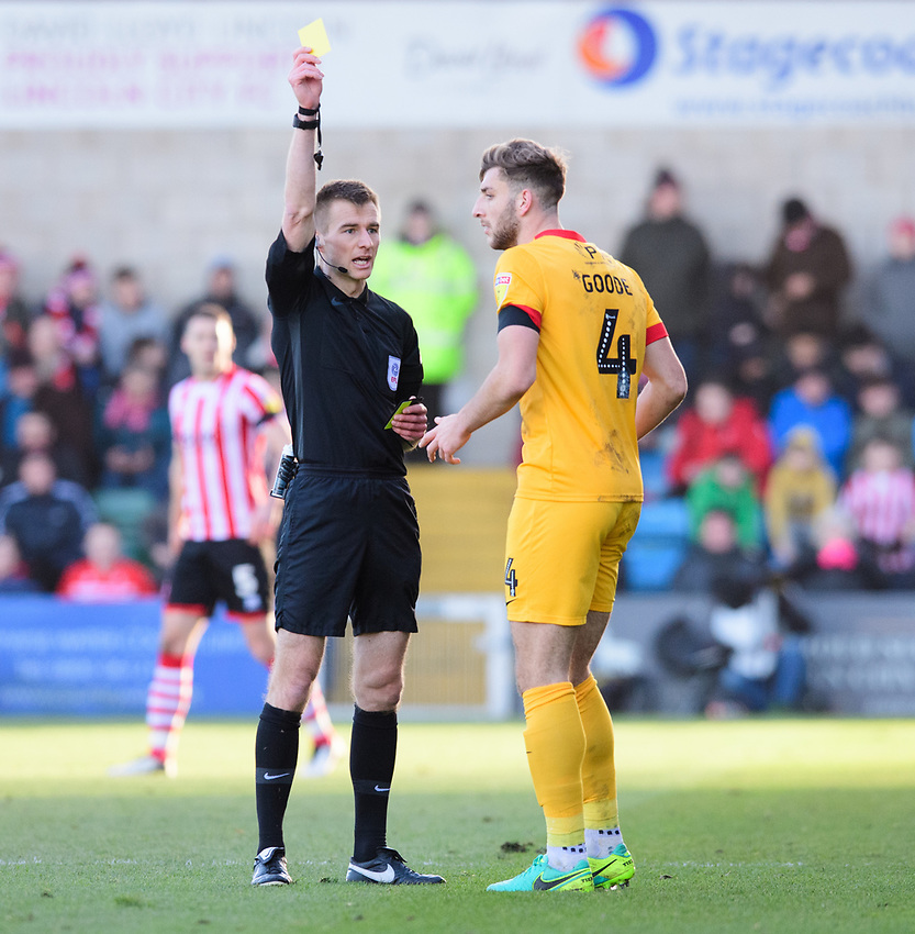 Northampton Town's Charlie Goode is shown a yellow card by referee Michael Salisbury<br /> <br /> Photographer Chris Vaughan/CameraSport<br /> <br /> The EFL Sky Bet League Two - Lincoln City v Northampton Town - Saturday 9th February 2019 - Sincil Bank - Lincoln<br /> <br /> World Copyright © 2019 CameraSport. All rights reserved. 43 Linden Ave. Countesthorpe. Leicester. England. LE8 5PG - Tel: +44 (0) 116 277 4147 - admin@camerasport.com - www.camerasport.com