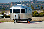 Airstream trailer on runway with hill in the background