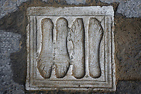 Detail of Ex-voto plaque, Italica, Seville, Spain, pictured on December 28, 2006, in the morning. An ex-voto is a simple devotional sculpture, an offering of gratitude to a God who has helped a certain body part, or a vow of faith. Presumably this Roman was grateful to a God for the healing of feet. Italica was founded by Scipio Africanus in 206 BC as a centre for soldiers wounded in the Battle of Ilipa, a defeat for Carthage during the Punic Wars, and became a military outpost. The name signifies that the original settlers were from an Italian regiment. It was one of the first cities in Roman Hispania and was the birthplace of two Roman Emperors: Trajan (53-117 AD) and Hadrian (76-138 AD). The city declined after the fall of the Roman Empire. Picture by Manuel Cohen.