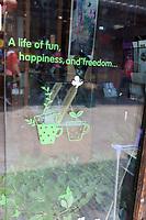 Yangzhou, Jiangsu, China.  Dong Guan Street.  Message on a Shop Window: Fun, Happiness, Freedom.