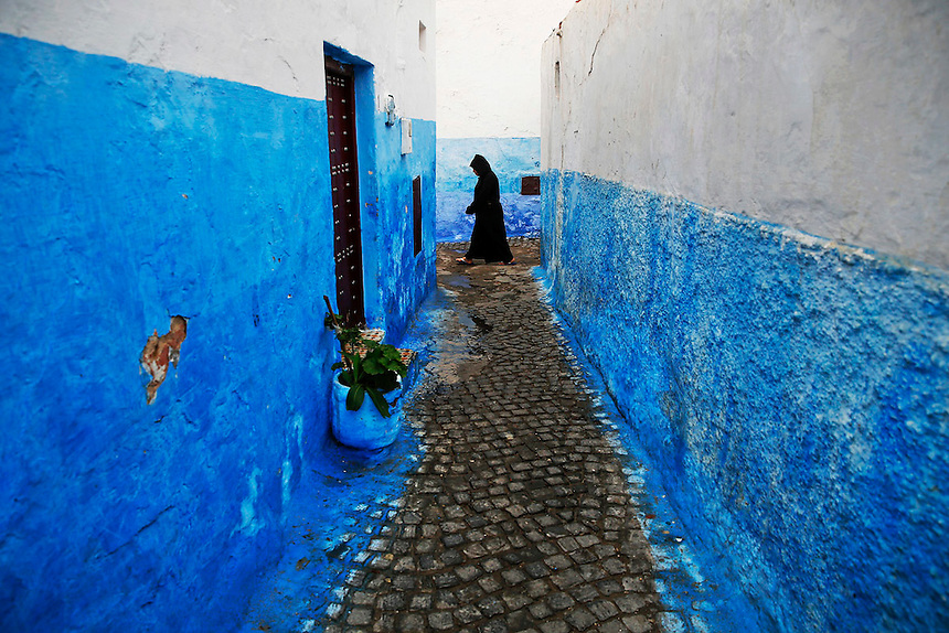 "A woman makes her way between houses painted in traditional blue and white colors in Kasbah of the Oudayas, a picturesque ancient part of Rabat September 21, 2014. Kasbah of the Oudayas, now home to about 2000 people, was built as a fortress by Almohad dynasty in 12th century at the mouth of the great Bou Regreg river. Behind walls of Medina and Kasbah of the Oudayas, ancient neighbourhoods of Morocco's capital, labyrinths of small alleys, colourful buildings and street markets offer a glimpse into city's rich history. Rabat was recently listed by UNESCO as a World Heritage Site and suggested as a ""must see"" destination by major media outlets and tourist agencies.  REUTERS/Damir Sagolj (MOROCCO)"