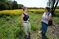 NWA Democrat-Gazette/ANDY SHUPE<br /> Terri Lane (left), executive director of the Northwest Arkansas Land Trust, speaks Saturday, Sept. 7, 2019, with visitor Suzan Plyler of Fayetteville during a tour of the Wilson Springs Preserve in Fayetteville. The Northwest Arkansas Land Trust has been working for seven years to preserve and restore the 121-acre prairie wetland and opened the area to visitors with Immerse, a nature and arts festival.