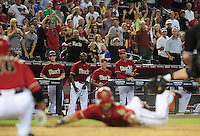 Jun. 20, 2012; Phoenix, AZ, USA; The Arizona Diamondbacks bench and fans look on as third baseman Ryan Roberts slides safely into home after hitting a two run inside the park home run in the sixth inning against the Seattle Mariners at Chase Field.  Mandatory Credit: Mark J. Rebilas-