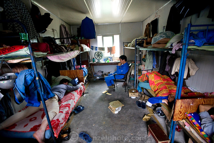Workers rest in the living quarters of a construction company in the fast-growing Pudong area of Shanghai, China. (From the coverage of welder Huang Neng in the book What I Eat: Around the World in 80 Diets.) Living quarters and food services are on site, and at least 10 workers share one room. In China, migrant laborers often live directly on the job-site grounds of big construction projects and work 12-hour shifts, seven days a week. Alcohol is only tolerated in the company cafeteria after dinner.