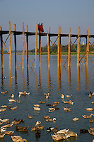 Monks crossing the U-Bein Bridge, the teakwood bridge spans 1.2 km across the shallow Taungthaman Lake some 10 km south of Mandalay. Amanpura, Mandalay, Myanmar/Burma