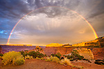 A full rainbow at sunset with streaking clouds in Canyonlands National Park with Dead Horse Point in the background, near Moab, Utah.
