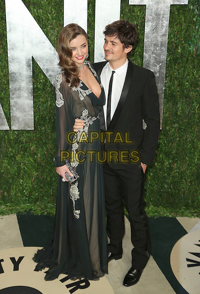 Miranda Kerr, Orlando Bloom.2013 Vanity Fair Oscar Party following the 85th Academy Awards held at the Sunset Tower Hotel, West Hollywood, California, USA..February 24th, 2013.oscars full length black dress vintage sheer overlay embellished floral design low cut plunging neckline cleavage arm around waist suit white shirt couple .CAP/ADM/SLP/DOW.©Dowling/StarlitePics/AdMedia/Capital Pictures