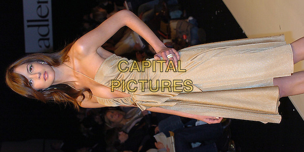 MODEL.London Fashion Week Autumn/Winter 2005/6 at the Royal Academy of Arts..Ben de Lisi Fashion Show .February 13th 2005.full length catwalk beige halterneck dress plunging neckline hand on hip scarf for belt.www.capitalpictures.com.sales@capitalpictures.com.©Capital Pictures