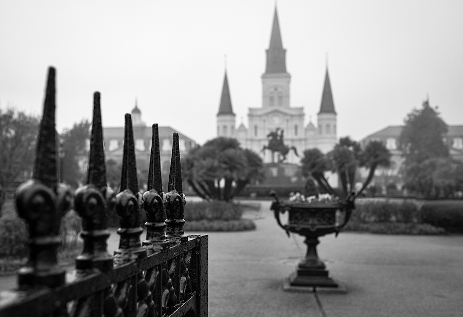View of entrance and iron fence around Jackson Square in New Orleans with the St. Louis Cathedral behind.