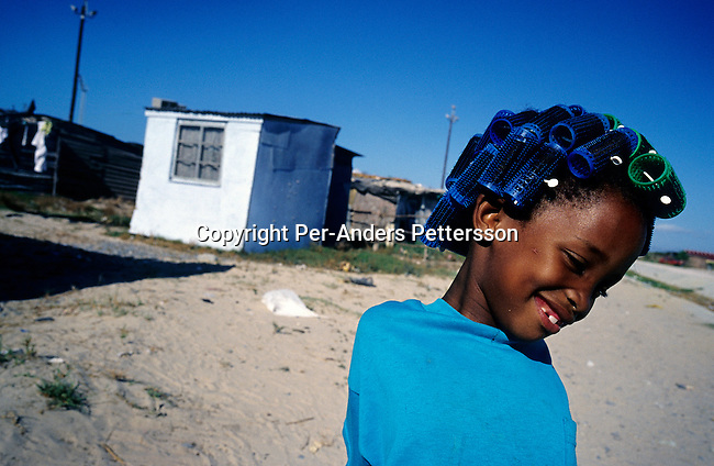 A young girl with colorful spools in her head on August 11, 2001 in the Mufuleni section in Khayelitsha, a township outside Cape Town, South Africa. Khayelitsha is one of the poorest and fastest growing townships in South Africa. People come from rural areas in Eastern Cape province to find work as maids and laborers. Most people don't find work and the unemployment rate is very high. (Photo by: Per-Anders Pettersson).