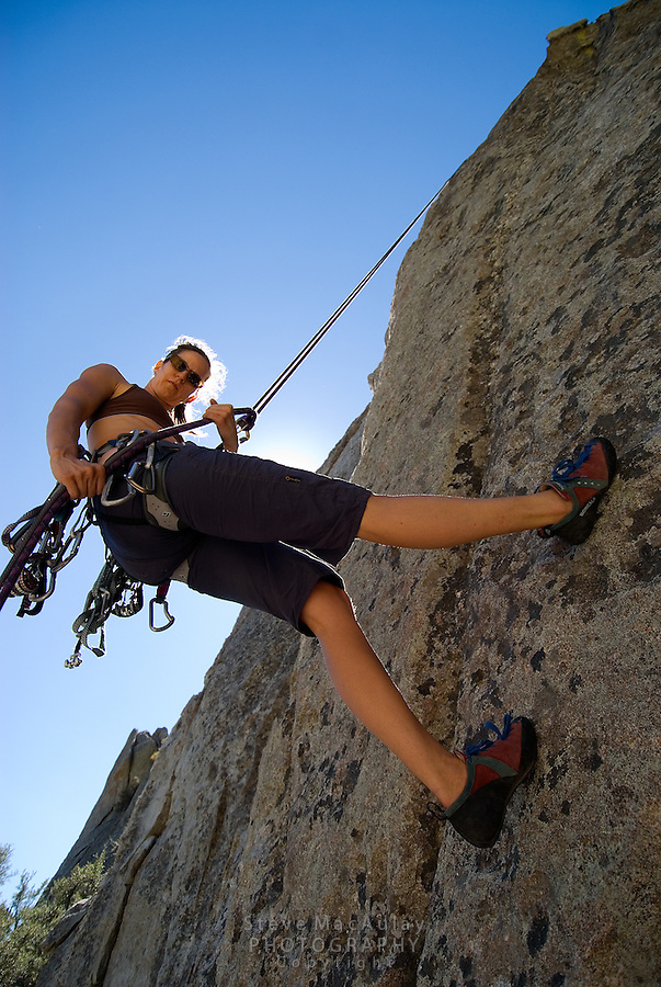 Young woman rapelling down cliff face after rock climbing, City of Rocks, Idaho