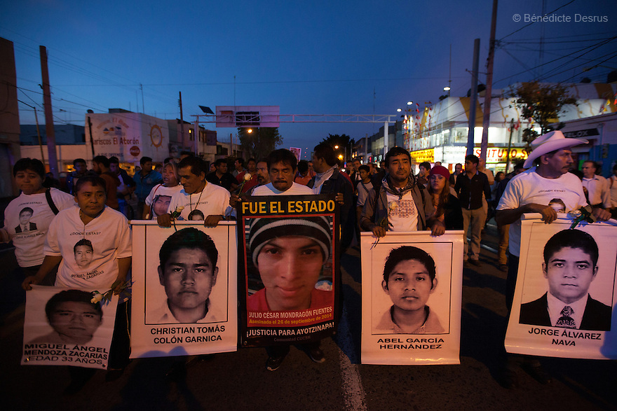 """Parents and relatives of the 43 missing students from Ayotzinapa's teacher training college hold images of the missing students and signs saying """"It was the state"""" during a march in Guadalajara, Jalisco, Mexico on November 18, 2014. The relatives of the 43 missing students still do not believe the official line that the young men are all dead, and with classmates, social organizations and human rights defenders, they started on Thursday a national caravan. They split up into three different caravans, branching out to share information face to face with supporters in other cities and rally nationwide support. The three groups will meet in Mexico City on Thursday 20 for a general strike and massive marches to demand justice and fight against corrupted government and organized crime. Criticism of the government has intensified in Mexico, and many are demanding that the search for the 43 missing students continue until there is concrete evidence to the contrary. (Photo by BénédicteDesrus)"""