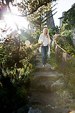 USA, California, Big Sur, Esalen, a woman walks down the stairs leading to the deck below the Murphy House, the Esalen Institute