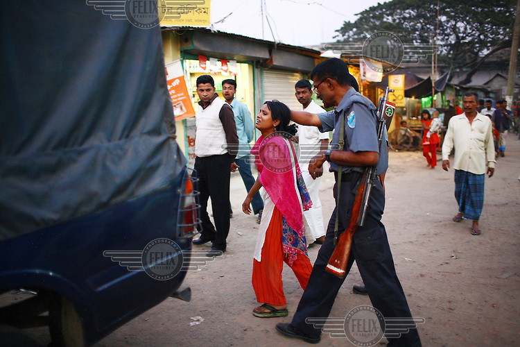 A policeman dragging a young sex worker to a van after she was arrested for involvement in child trafficking.