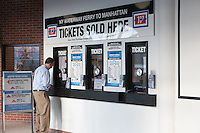 A commuter purchases a ticket at a NY Waterway Ferry ticket window located in the Hoboken/NJ Transit Terminal