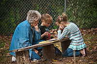 Janice Mosher helps her grandchildren, Codi, left, and Kayla Mosher play checkers at the annual Ned Mosher Apple Butter Festival. The festival held at the Knox-Metzker log cabin on the grounds of McVay Elementary School in Westerville every year helps raise money to maintain the cabin as a teaching tool for students at the school.