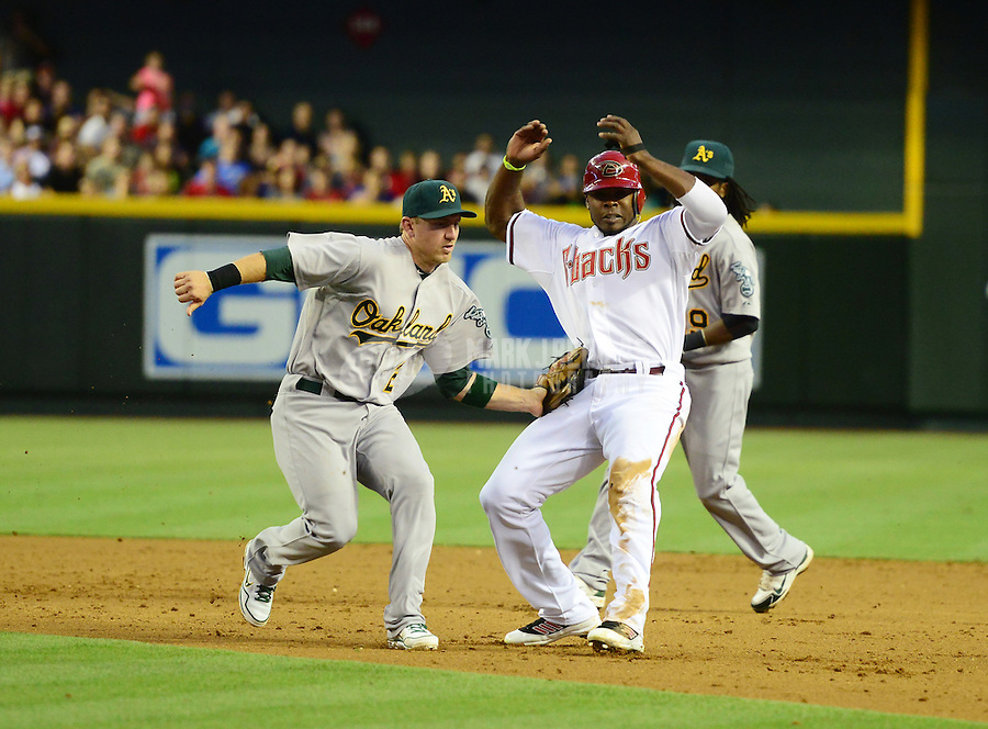 Jun. 8, 2012; Phoenix, AZ, USA; Arizona Diamondbacks base runner Justin Upton (right) is tagged out by Oakland Athletics shortstop Cliff Pennington during a second inning rundown at Chase Field.  Mandatory Credit: Mark J. Rebilas-