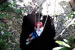Girl rapelling into dark cave in jungle on adventure vacation