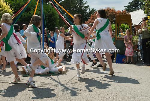 Children dancing around a May Pole Petersham village fete Richmond Surrey UK. Multi ethnic Britain.