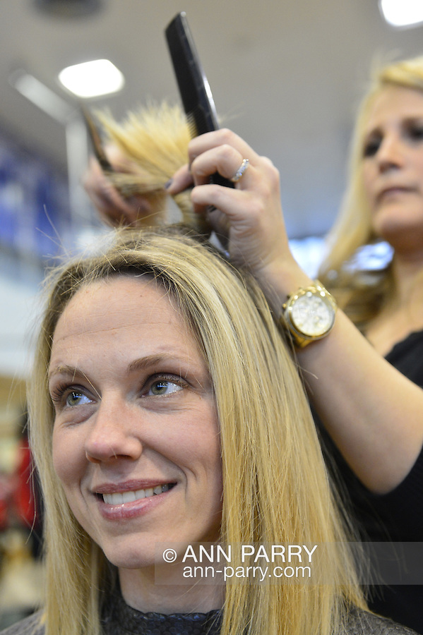 WENDY SIMSON, a teacher at Calhoun High School, is having haircut by BRENDA GALLO, a graduate of Calhoun, at the school's St. Baldrick's fund raising event. Simson is participating to honor her cousins who died of melanoma and cervical cancer. The Long Island school  exceeded its goal of raising $50,000 for childhood cancer research. Plus, many ponytails cut off, such as Simson's, will be donated to Locks of Love foundation, which collects hair donations to make wigs for children who lost their hair due to medical reasons.