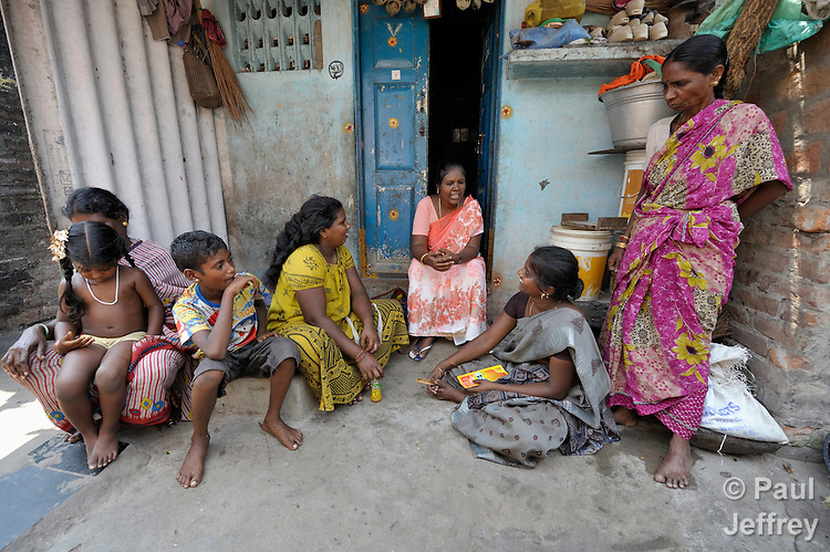 Percial (center), an educator with the Madras Christian Council of Social Service, talks with residents of a slum in Chennai, India, about HIV and AIDS and how HIV is transmitted.