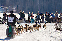 Allen Moore runs on Long Lake past spectarors having a picnic during the Restart of the 2016 Iditarod in Willow, Alaska.  March 06, 2016.