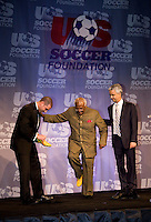 Adidas' Antonio Zea helps Archbishop Desmond Tutu try on a pair of personalized soccer cleats with the assistance of US Soccer President Sunil Gulati during the US Soccer Foundation Gala held at City Center in Washington, DC.