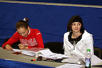 Marina Shpekt of Russia and Anna Bessonova of Ukraine smile while completing press information forms before 2006 Deriugina Cup Grand Prix event at Kiev, Ukraine on March 16, 2006. (Photo by Tom Theobald)