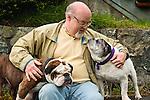 A man enjoys time with his bulldogs, Washington.