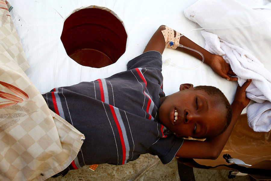 Nov 10, 2010 - Port-au-Prince, Haiti.A young patients suffering from cholera-like symptoms receives medical treatment in a small, crowded medical clinic set up in tents in the Cite Soleil area of Port-au-Prince, Haiti, Wednesday, November 10, 2010 as fears of a cholera outbreak spread through the area just two days after cases of the infection were confirmed in the area, the poorest slum in Haiti's capital. Officials from the Pan American Health Organization warn that Haiti's cholera epidemic, spread primarily through consuming infected water and food, is likely to grow much larger in the wake of Hurricane Tomas.  (Credit Image: Brian Blanco/ZUMA Press) 1