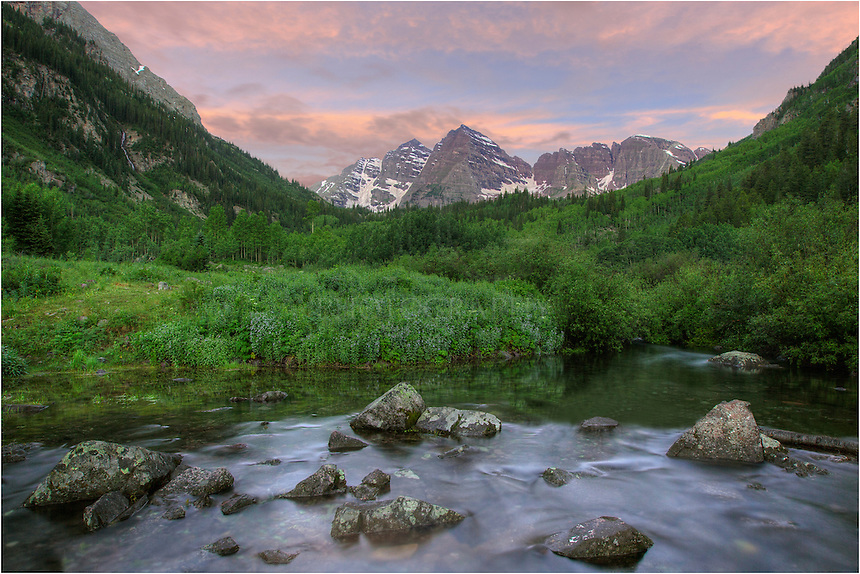 The clouds over Maroon and North  Maroon Peak were just beginning to show some color in this photograph from Colorado's iconic Maroon Bells area. Marook Creek was flowing all around me and I was perched, tripod and all, on a small rock about 4 feet above the water - all rather precariously. Still, I wanted to be in the middle of the action. Fortunately, the image came out nicely and I did not slip into the freezing waters. Behind me, the sun was just beginning to light up the valley and Maroon Lake was silent and still on this early morning in late July.