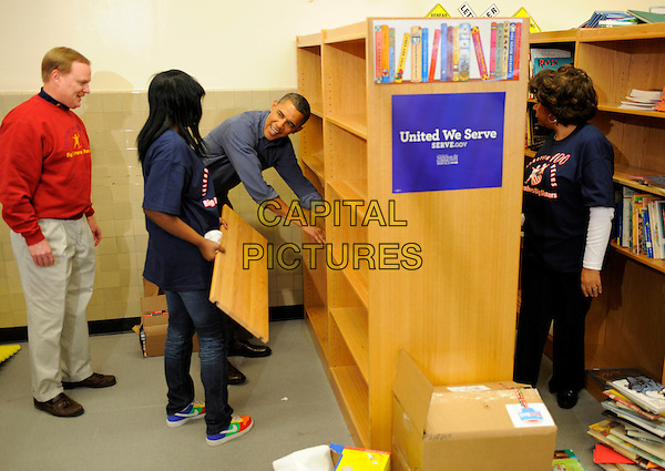 United States President Barack Obama (c) assists in putting in book shelves as he joins volunteers in a library as they participate in a service project, at Browne Education Center, in Washington, DC, USA, on the Martin Luther King Jr national holiday, 16 January 2012. The project was in memory of the legacy of community service, promoted by the late civil rights leader, who was assassinated in 1968.  .CAP/ADM/MT.©Mike Theiler/Pool/CNP/AdMedia/Capital Pictures.