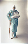 man standing with crutch and with casts, bandaged arm, leg and head