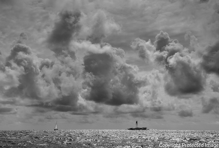 Dramatic clouds high over a lighthouse and a sailboat in the open ocean.