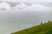 Two people walk over downland near the Seven Sister cliffs in the South Down of Sussex. The South Downs and the UK`s newest National Park and comprise an area of outstanding beauty on the Sussex coast. July 2002