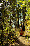 An eight year old boy and six year old girl (brother and sister) stand along a trail in Bonner County, Idaho.