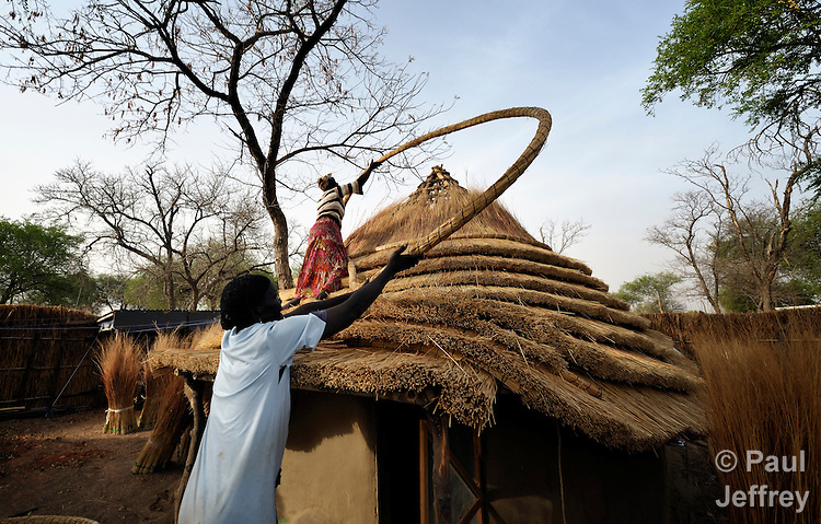 Gina Gial (below) and Mary Musiah construct a thatched roof in Agok, a town in the contested Abyei region where tens of thousands of people--including Gial and Musiah--fled in 2011 after an attack by soldiers and militias from the northern Republic of Sudan on most parts of Abyei. Although the 2005 Comprehensive Peace Agreement called for residents of Abyei--which sits on the border between Sudan and South Sudan--to hold a referendum on whether they wanted to align with the north or the newly independent South Sudan, the government in Khartoum and northern-backed Misseriya nomads, excluded from voting as they only live part of the year in Abyei, blocked the vote and attacked the majority Dinka Ngok population. The African Union has proposed a new peace plan, including a referendum to be held in October 2013, but it has been rejected by the Misseriya and Khartoum. The Catholic parish of Abyei, with support from Caritas South Sudan and other international church partners, has maintained its pastoral presence among the displaced and assisted them with food, shelter, and other relief supplies.