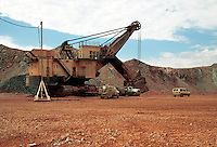 Open pit copper mine, a shovel loads ore onto trucks. Arizona.